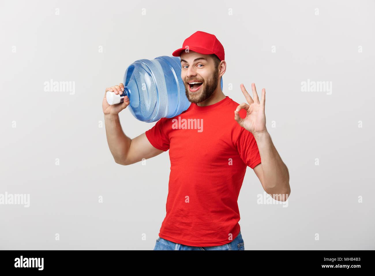 Portrait smiling bottled water delivery courier in red t-shirt and cap carrying tank of fresh drink and showing ok isolated over white background. Stock Photo
