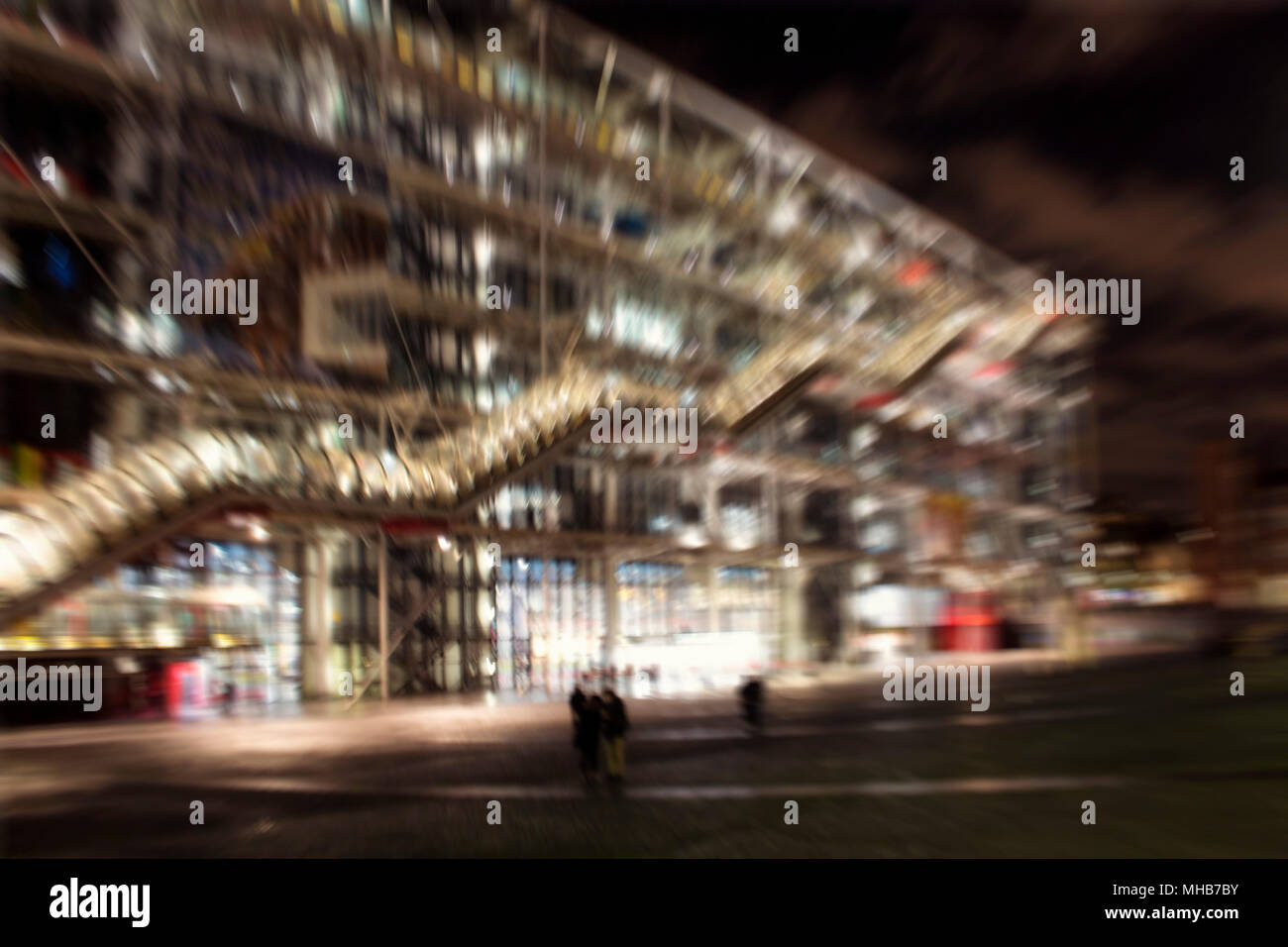 Blurry Motion Image Of People Walking In Front Of A Modern
