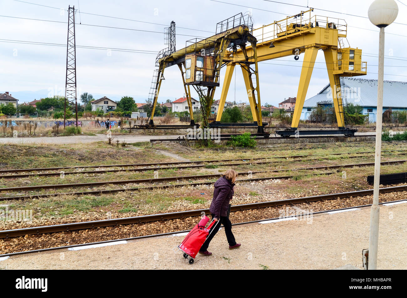 Bulgarian woman and a bag in a rural train station between Sofia and Plovdiv, Bulgarian State Railways (BDZ) in Sofia, Bulgaria - Stock Image
