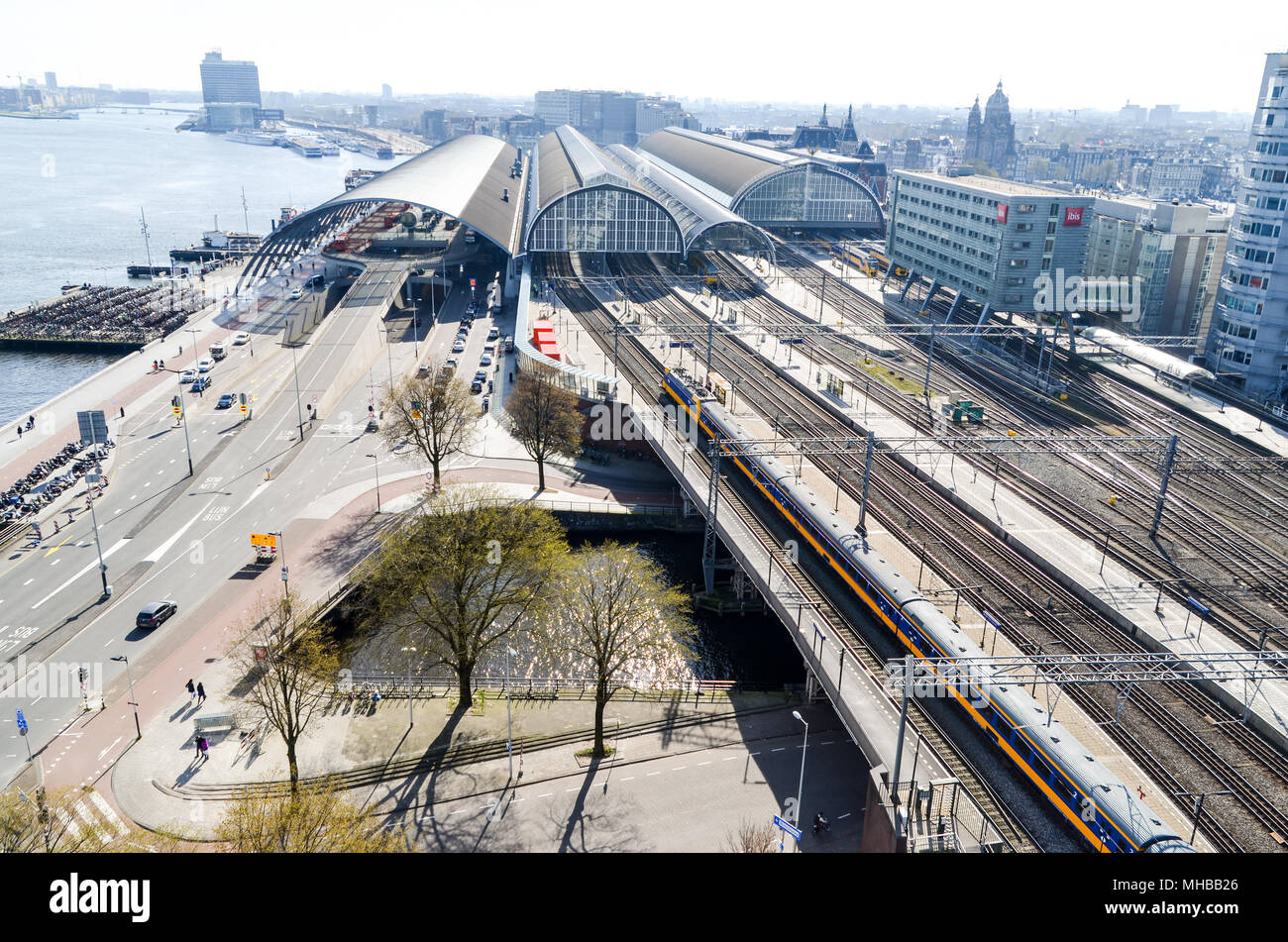 Aerial view of Amsterdam and Centraal Station showing mobility solutions (trains on railways, cars on roads, ferries on waterways), Amsterdam - Stock Image