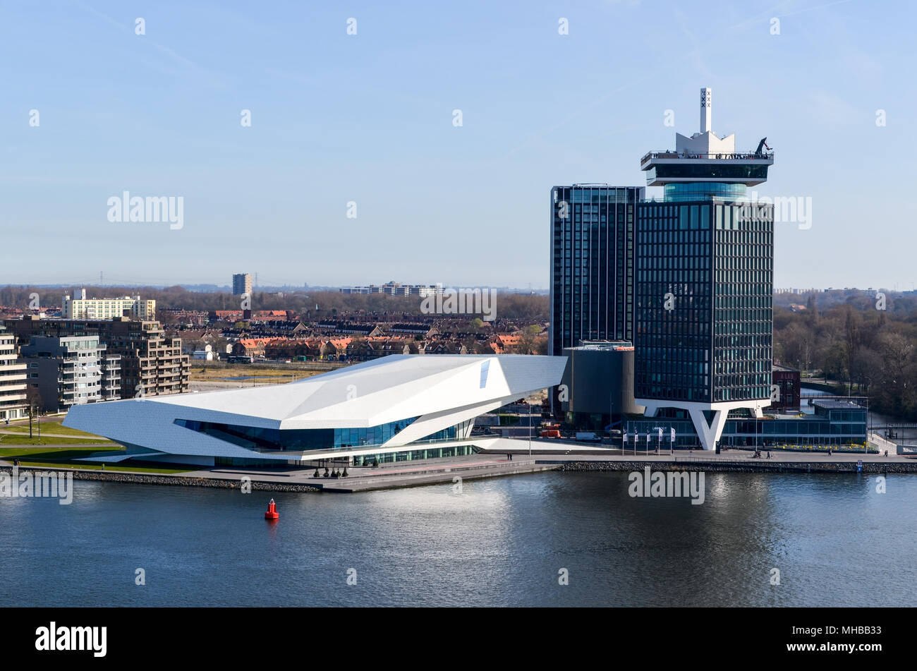 Aerial view of the EYE museum and the A'DAM Lookout tower, framed with blue sky and the IJ river, Amsterdam, Netherlands - Stock Image