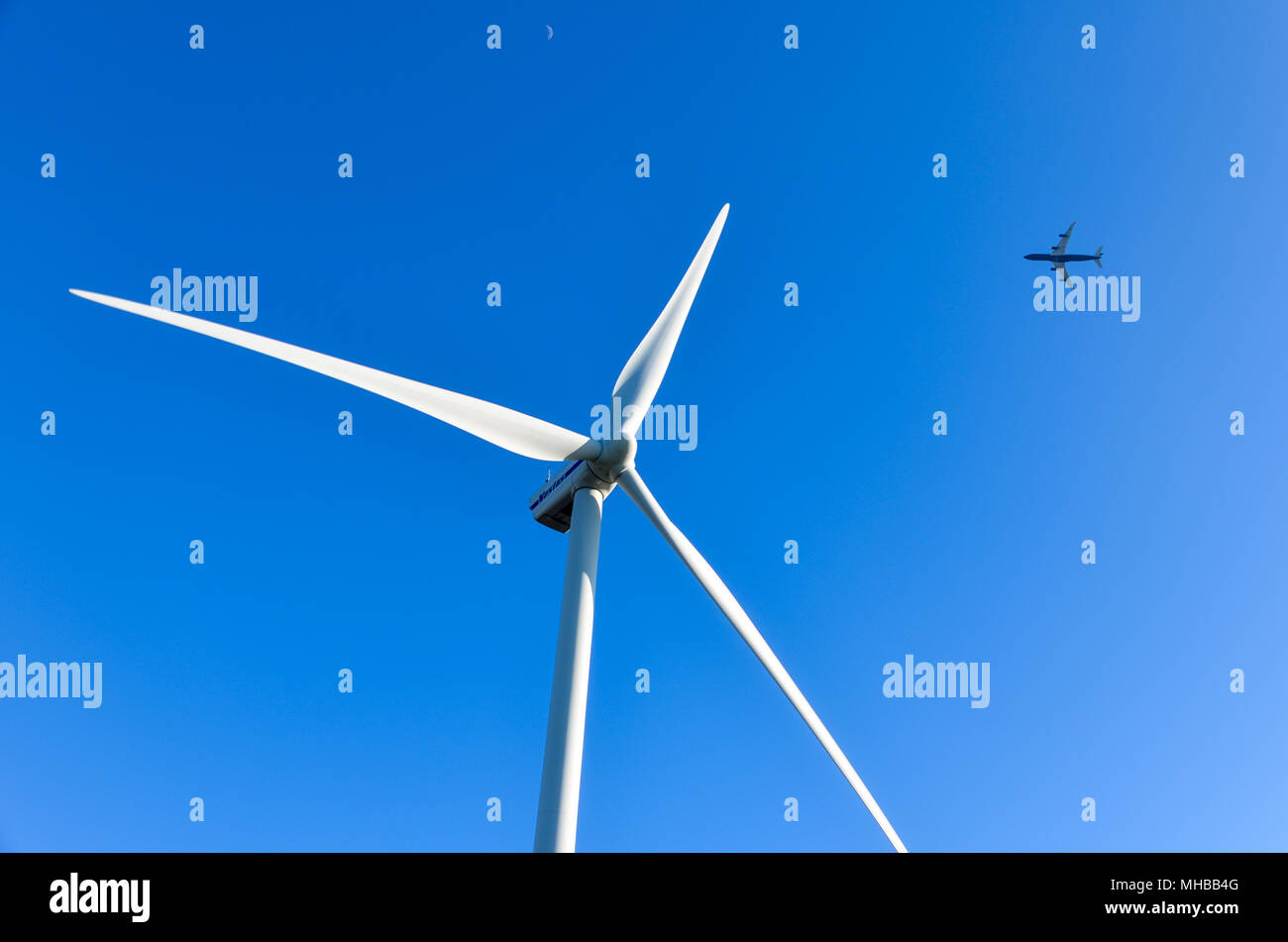 Plane flying behind a wind turbine on a blue sky background - Stock Image