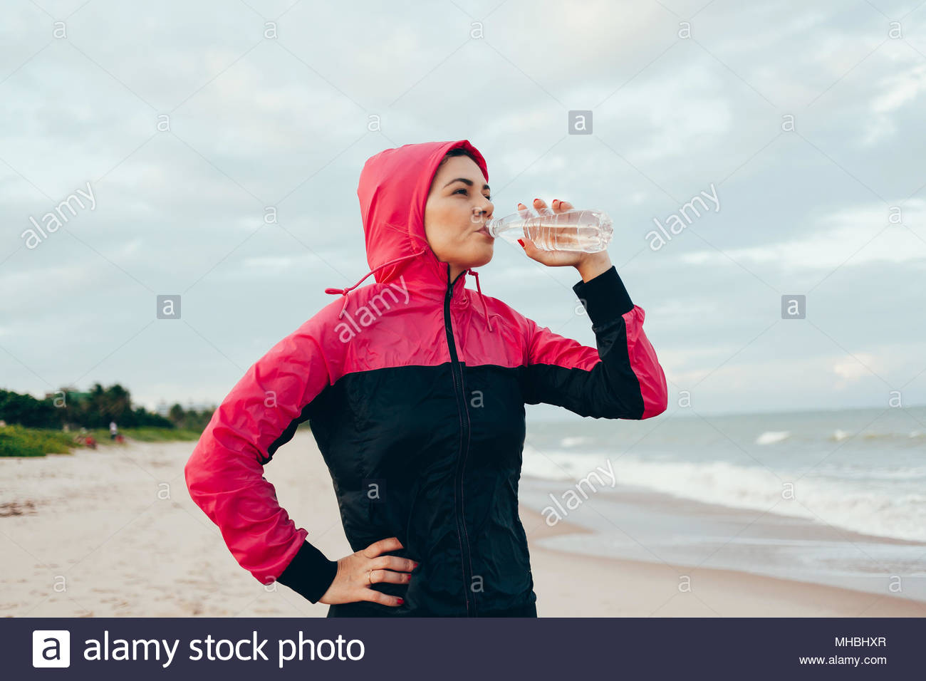 Fitness runner woman drinking water of a sport bottle. Athlete girl taking a break during run to hydrate during hot summer exercise on beach. Healthy  - Stock Image