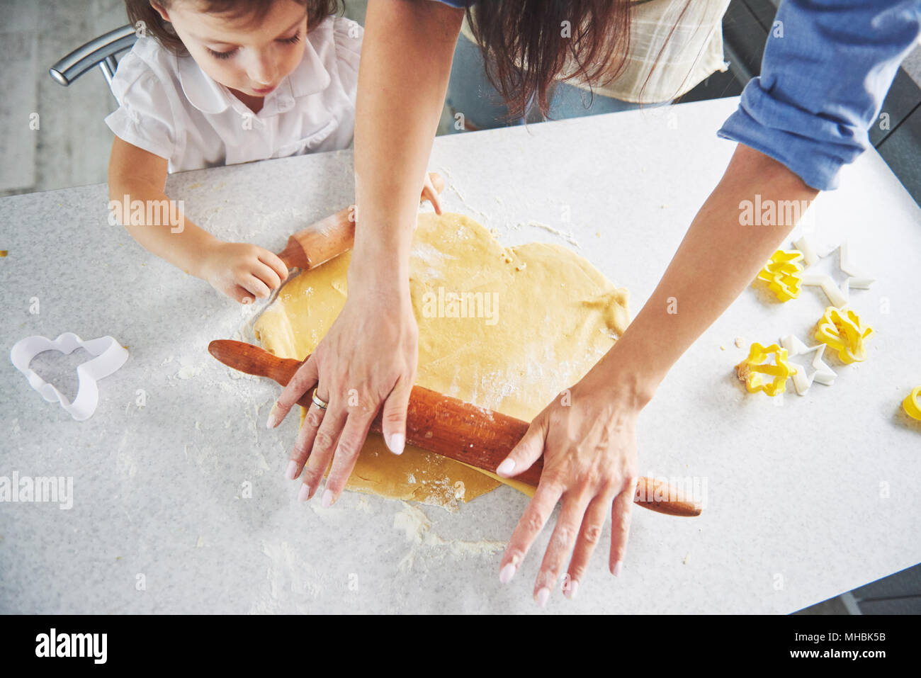 Happy family preparation holiday food concept. Family cooking Christmas cookies. Hands of mother and daughter preparing the dough on the table. Happy family in making cookies at home - Stock Image
