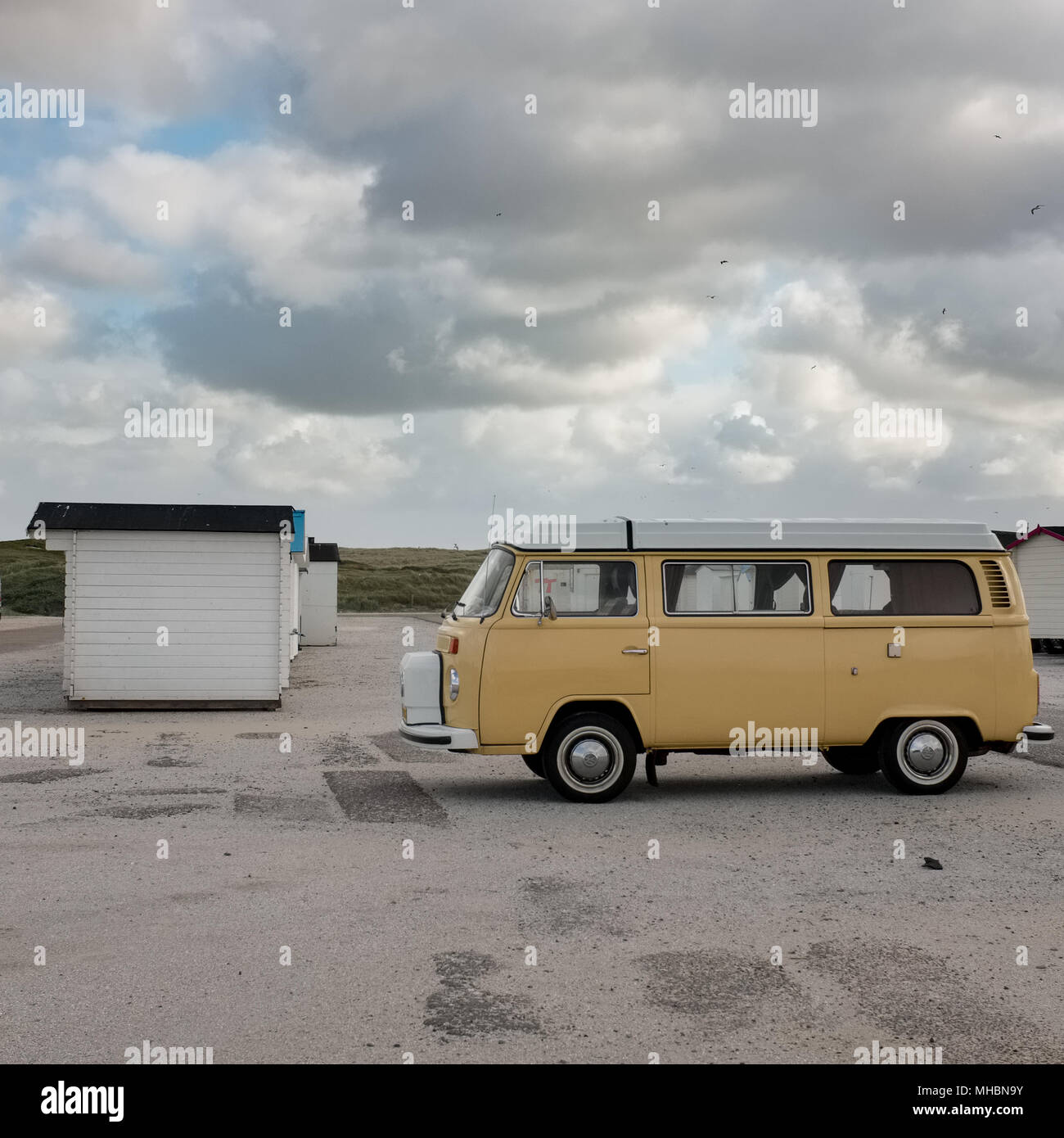 Old Volkswagen van and beach cabins on a deserted beach on Texel, the Netherlands. Stock Photo