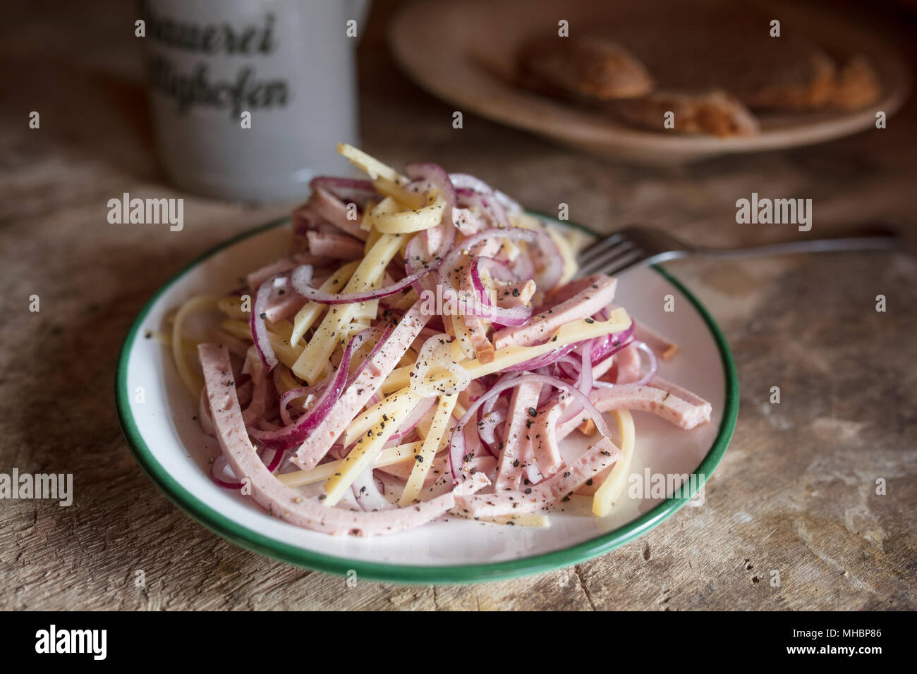 Swiss sausage salad, served in a plate on a wooden table, Bavaria, Germany - Stock Image