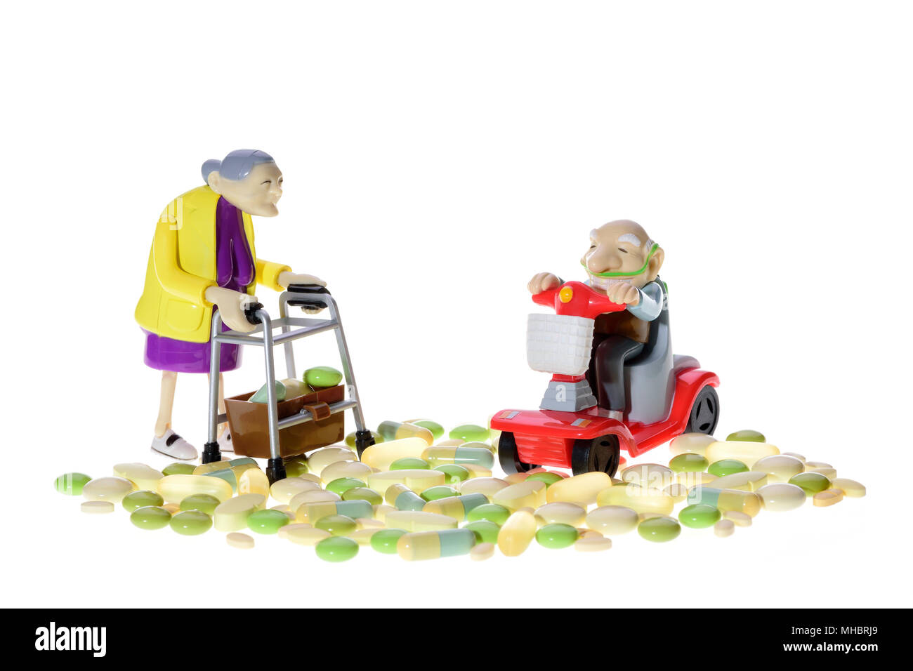 Figures, seniors with wheelchair and walker between different pills, symbol, white background - Stock Image