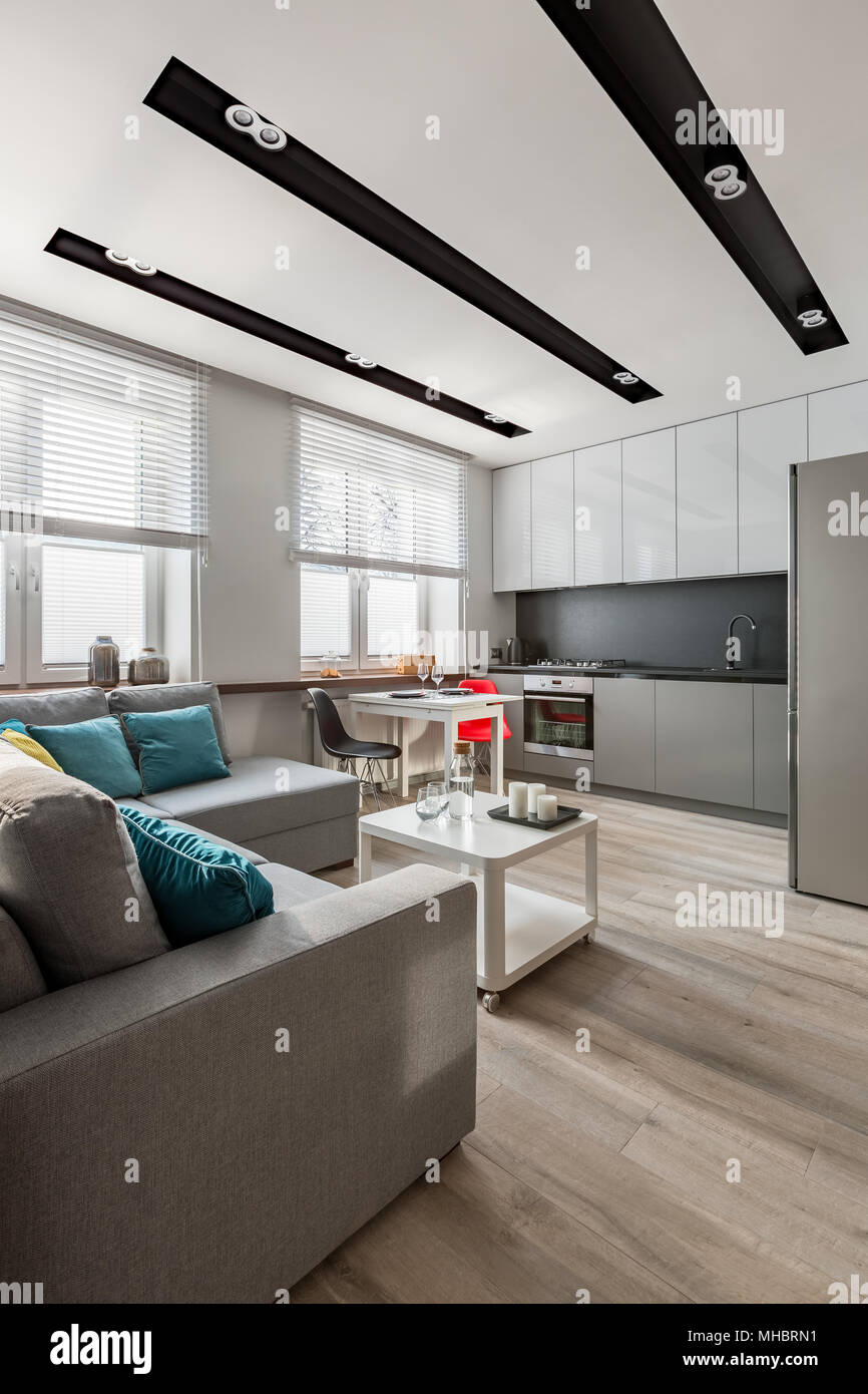 Apartment with modern ceiling led lamps, couch and open kitchen - Stock Image