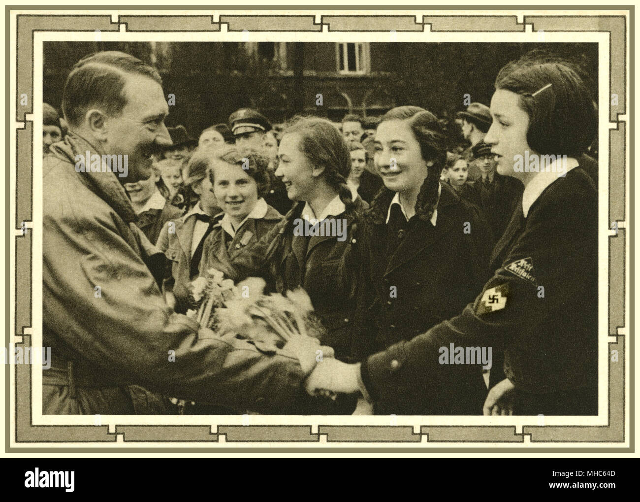 WWII 1939 Germany, Adolf Hitler Führer meeting impressionable teenage girls, the group leader in foreground, wearing a Swastika and rank badge, inducted into the 'Band of German Maidens ' (Bund Deutscher Mädel / BDM) wing of the Nazi Party Hitler Youth organization - Stock Image