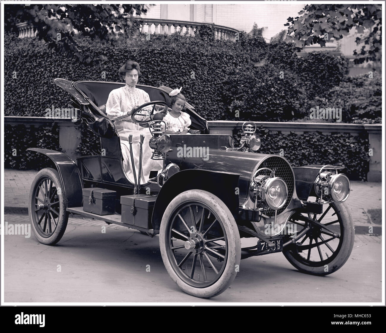 1907 Franklin Model D Roadster. Frank Bliven was a Washington, D.C. Franklin Auto dealer. Mrs. F.S. Bliven and daughter are featured. The Franklin Automobile Company produced vehicles from 1902 through 1934. They are best remembered for air-cooled engines, wooden frames, and full-elliptic springs.In 1907, the Model D was available as a four-person touring car, a two-person runabout, or a five-person Landaulette. The Model D rested on a wheelbase that measured 105-inches and powered by a four-cylinder engine that offered 20 horsepower The Great Depression was responsible for ending the brand. - Stock Image