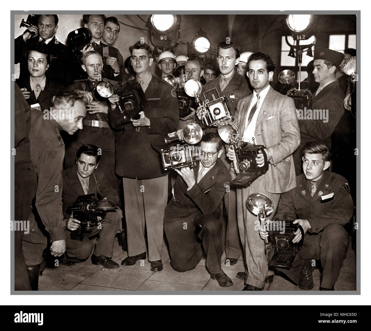 Photo-Journalists waiting for high ranking Nazis to exit the Nuremberg Trials court room.  Held for the purpose of bringing Nazi war criminals to justice, the Nuremberg trials were a series of 13 trials carried out in Nuremberg, Germany, between 1945 and 1949. The defendants, who included Nazi Party officials and high-ranking military officers along with German industrialists, lawyers and doctors, were indicted on such charges as crimes against peace and crimes against humanity, the most serious of which attracted a sentence of death by hanging... - Stock Image