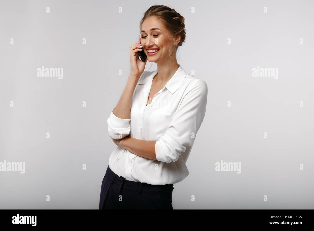 cheerful affable positive businesswoman dressed in white office shirt with a cell phone i business portrait on the gray background - Stock Image