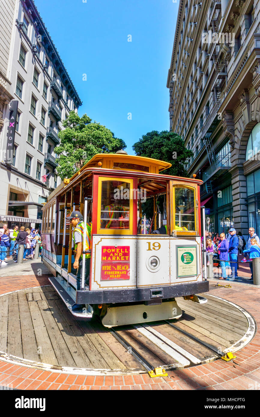 SAN FRANCISCO - APR 2, 2018: A worker rotates a cable car at the Powell and Market street turntable to pick up a crowd of passengers. A San Francisco  - Stock Image