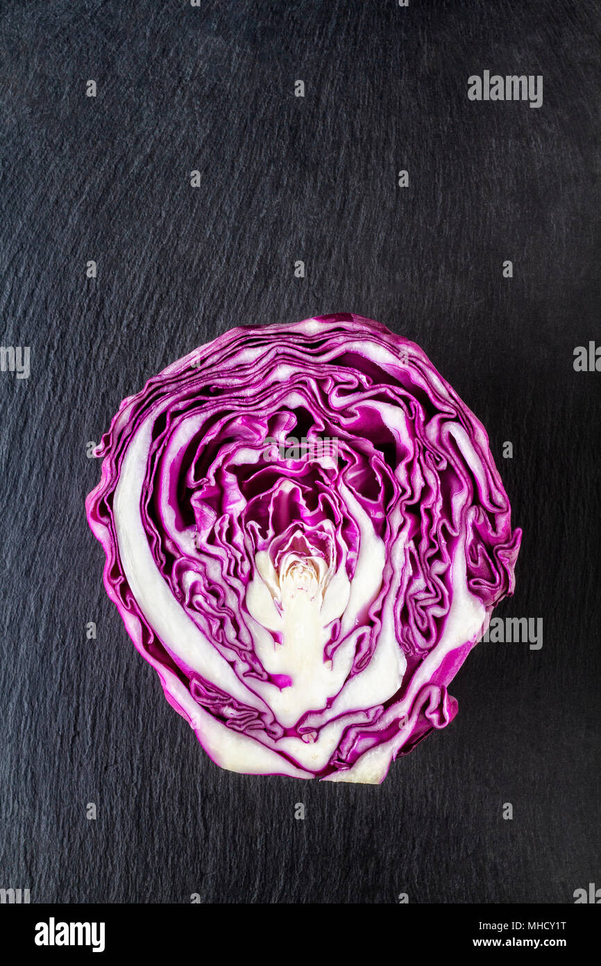 Purple cabbage.cut in half on a slate board - Stock Image