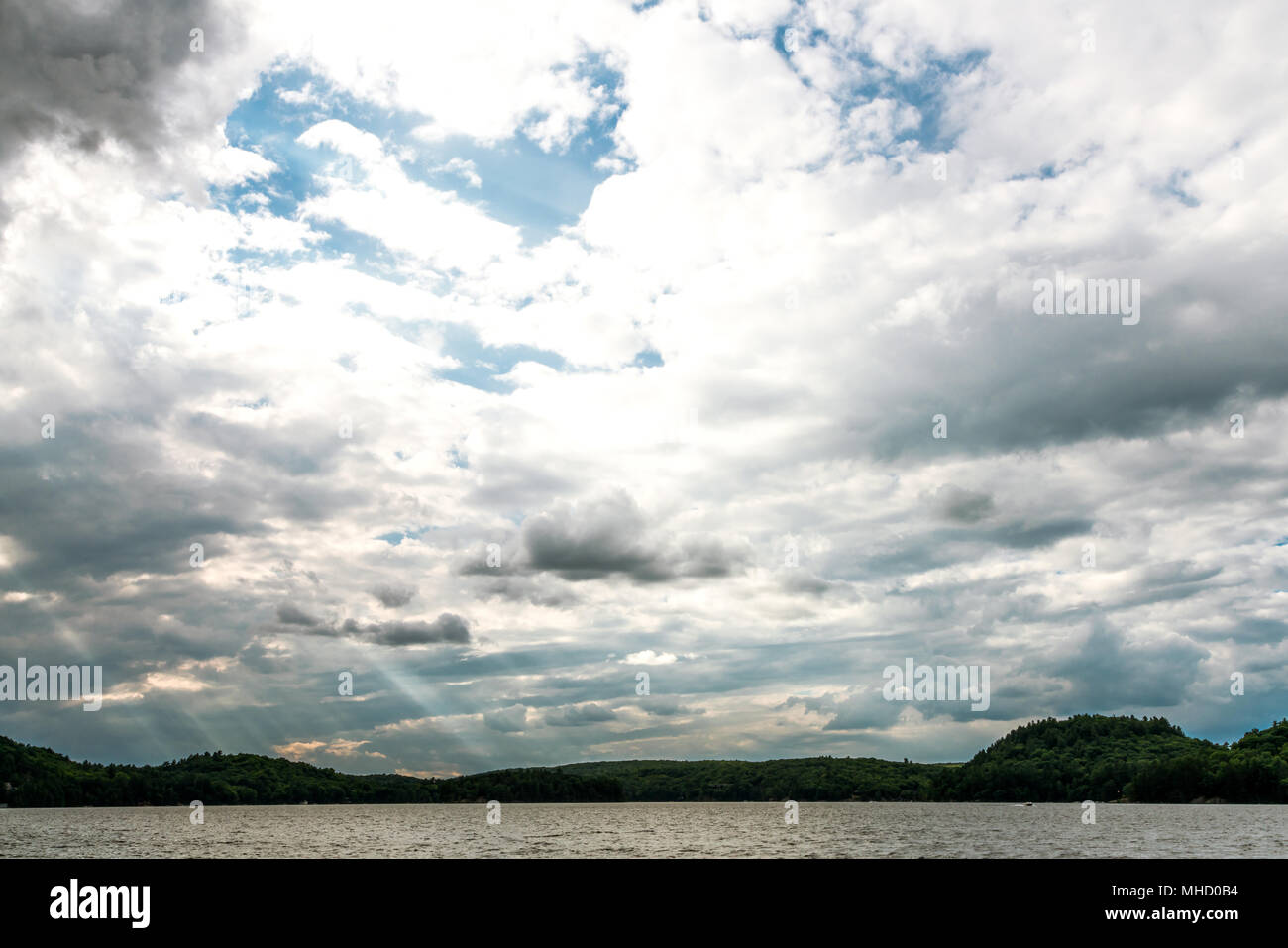 Clouds moving across a forested lake with the early evening sun rays breaking through Stock Photo