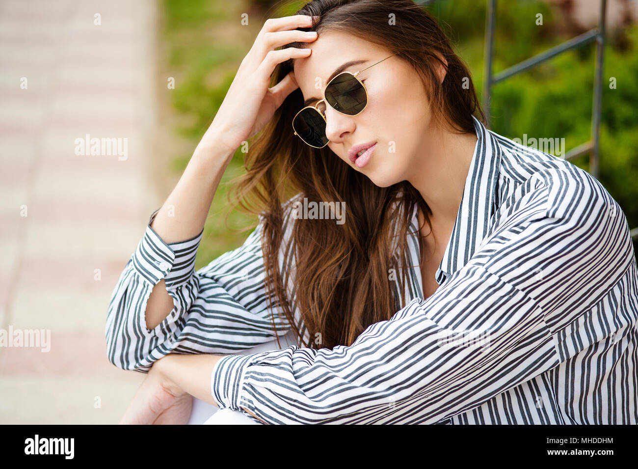 Portrait of pensive fair-haired dreamy hipster girl imagines something in her mind, looks upwards, being deep in thoughts, touching hair. Attractive young blonde female dreams about weekends - Stock Image