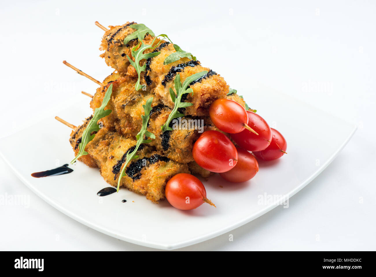 vegetables on skewer fried in batter decorated with tomatoes zucchini, eggplant, zucchini. white plate on white background - Stock Image