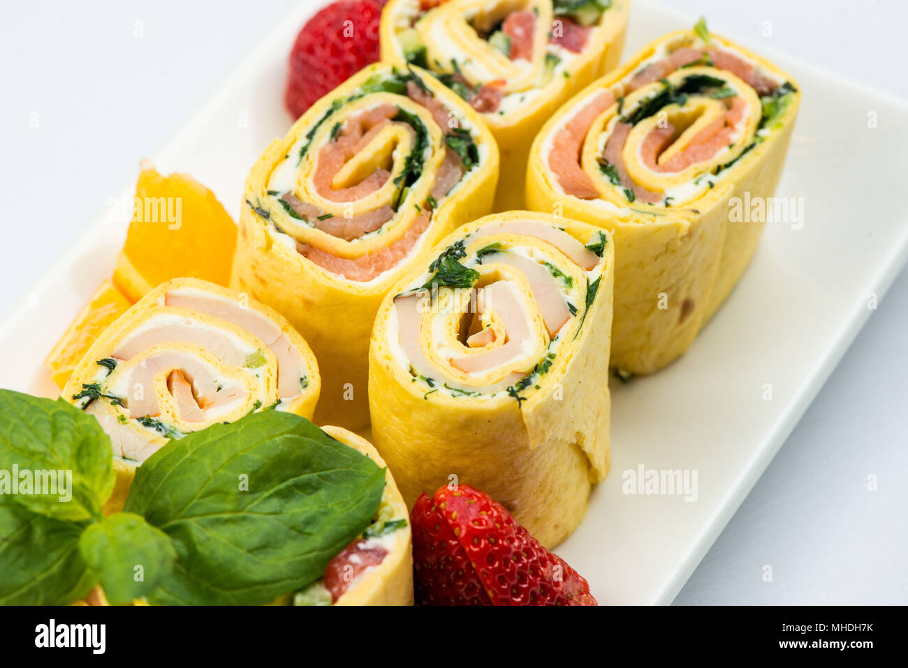 Rolls of thin pancakes with smoked salmon, horseradish cream cheese and rocket leaves on white plate on white background - Stock Image
