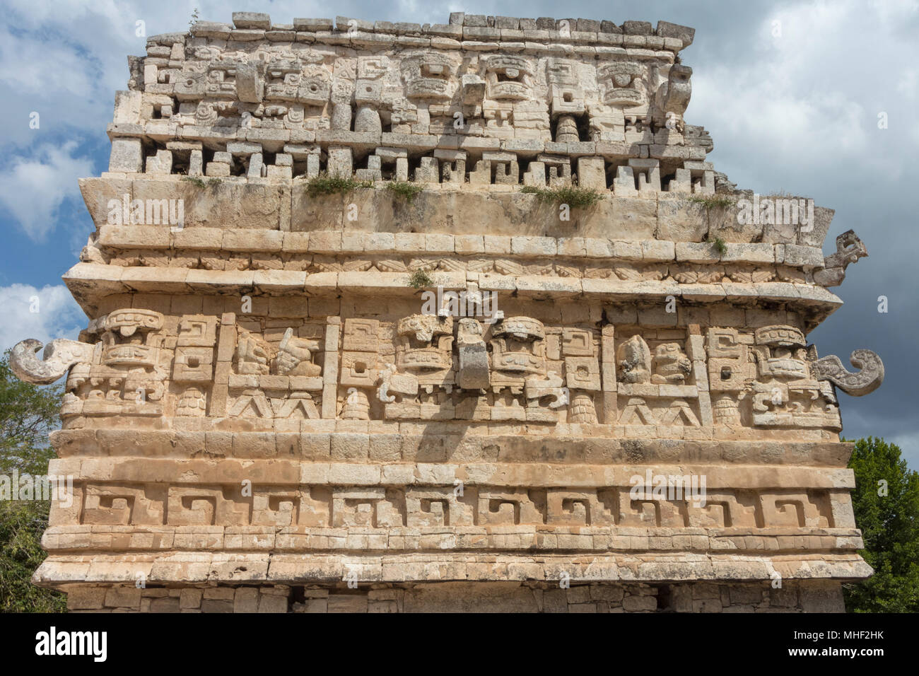 The magician's temple at Mayan ruins Chichen Itza. Impressive Stone building with carved details on every side. The Stone masks on the top floor still - Stock Image
