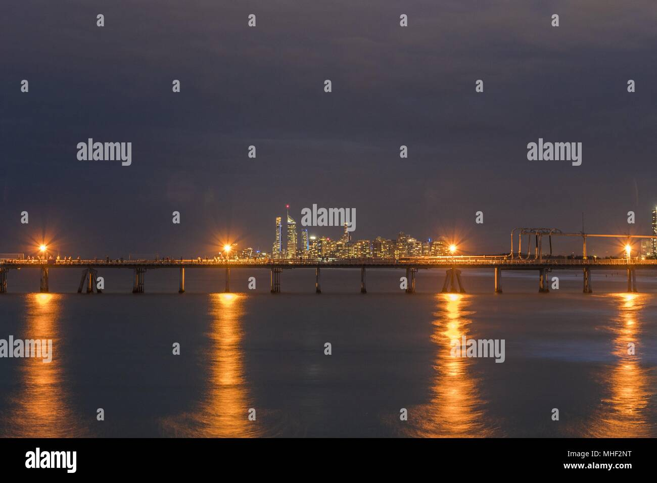The dusk glow from the Gold Coast reflects across the water with the lamps of a jetty in the midground painting lines in the blurred water. - Stock Image