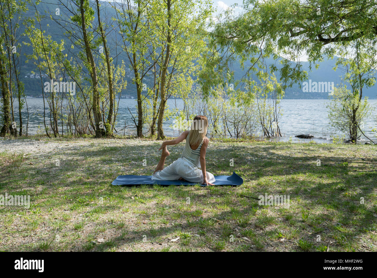 Young woman exercising yoga by the lake and mountains, shot in Ticino Canton, Switzerland, Europe. People relaxation wellbeing concept Stock Photo