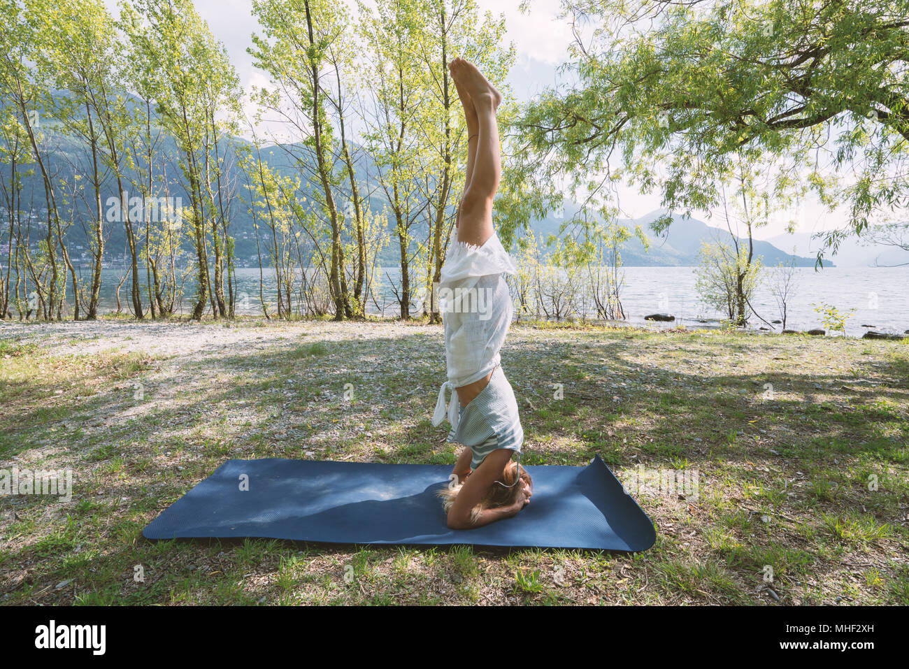Young woman exercising yoga by the lake and mountains, shot in Ticino Canton, Switzerland, Europe. People relaxation wellbeing concept - Stock Image