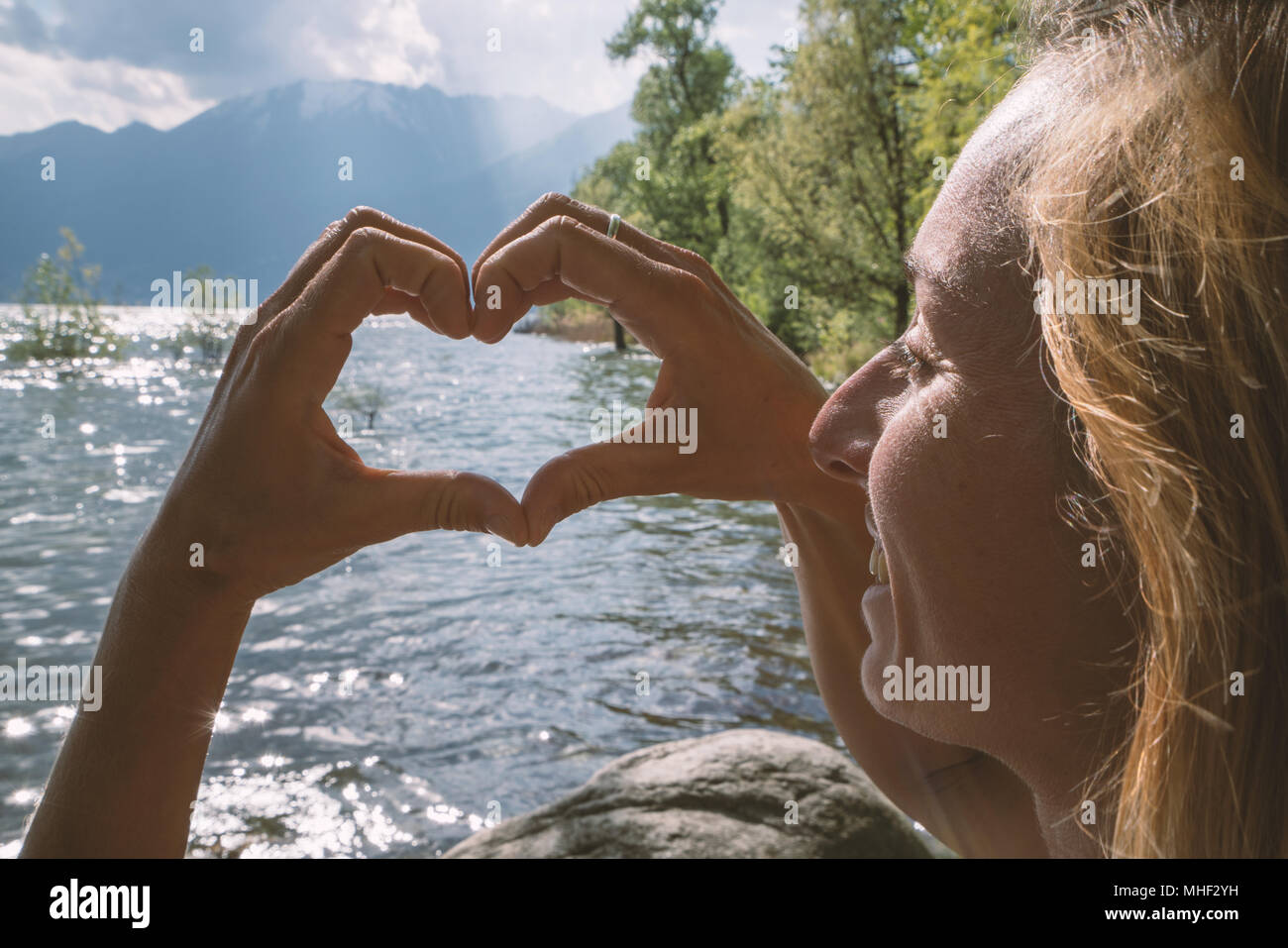 Young woman by the lake making heart shape with hands on mountain landscape, Shot in Ticino Canton, Switzerland, Europe. People travel environment Stock Photo