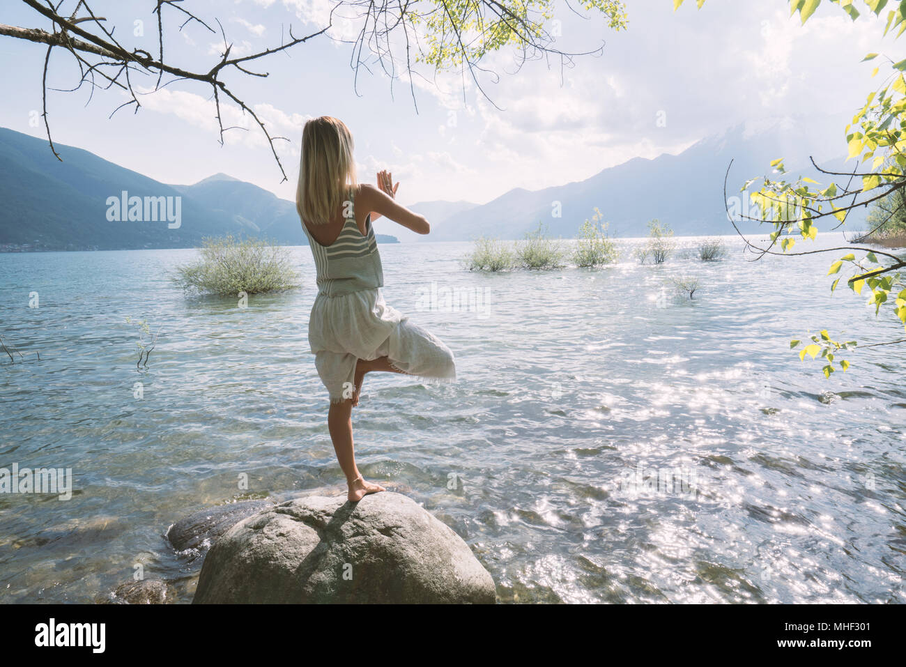 Young woman exercising yoga meditation and relaxation by lake shore in Ascona, Ticino, Switzerland, Europe. People travel wellbeing yoga zen concept Stock Photo