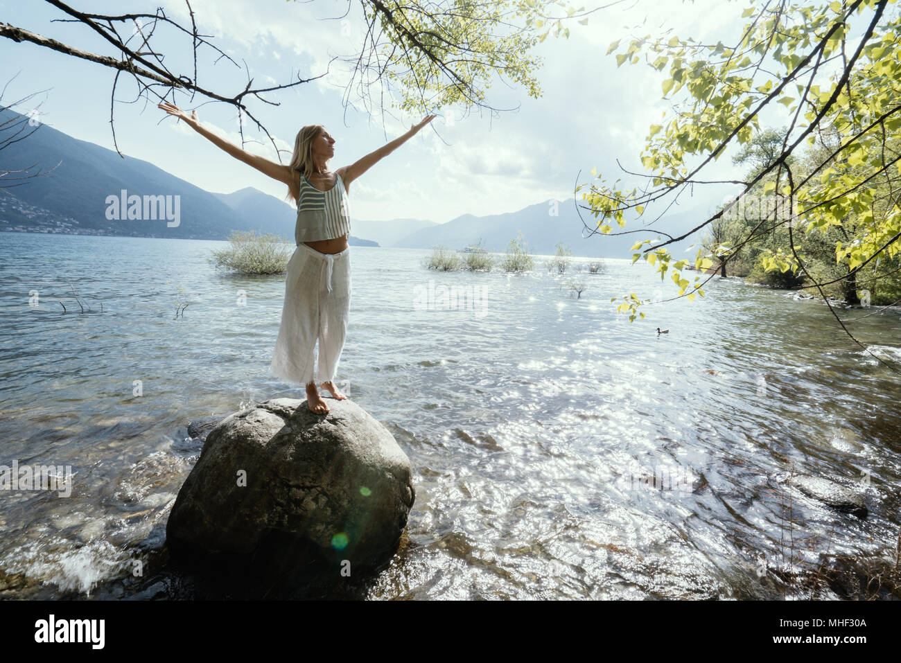 Young woman standing on rock above the lake arms outstretched for freedom and positive emotions. People travel wellbeing carefree concept. Switzerland Stock Photo