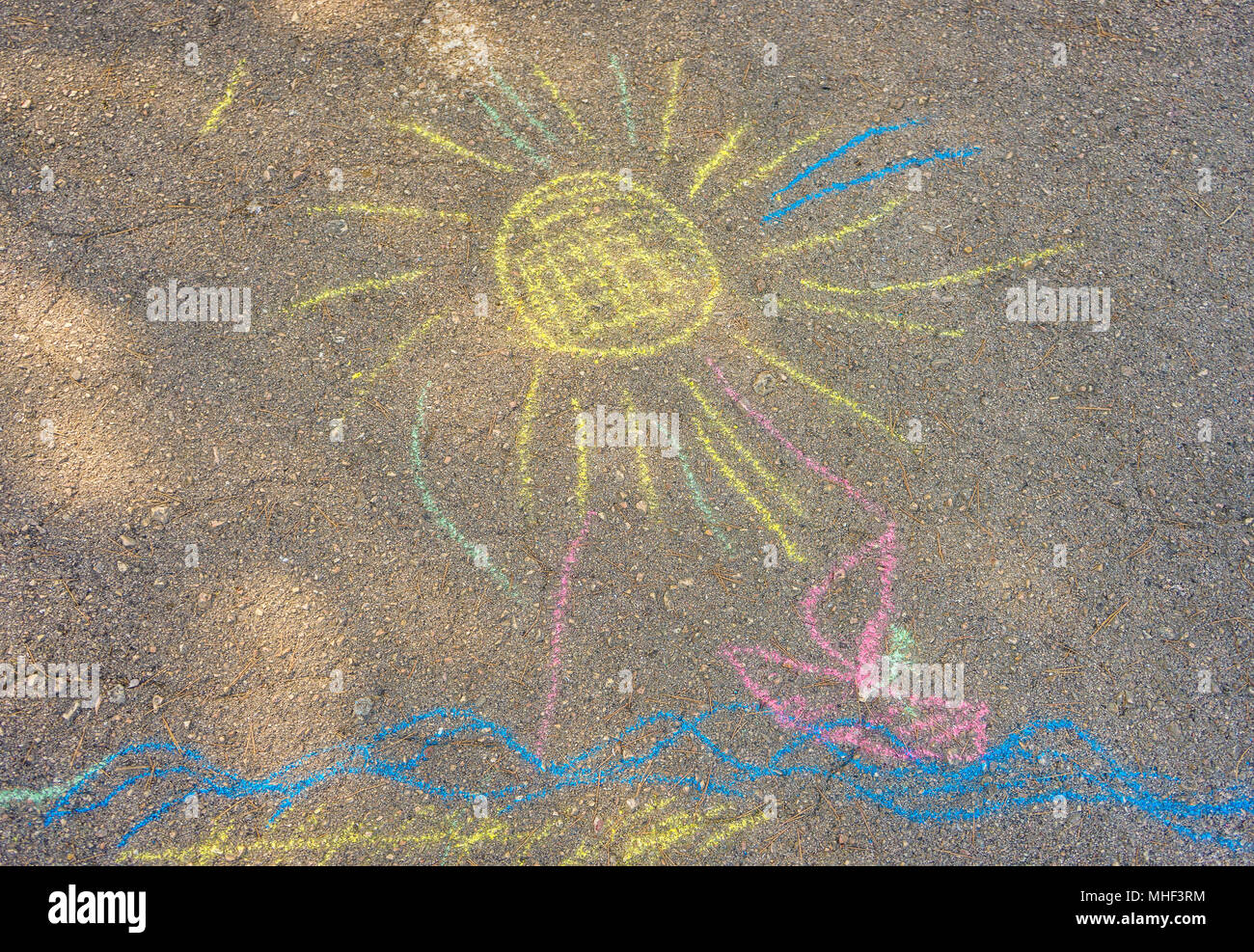 Children's drawing of the sea, the sun and the ship colored crayons on the asphalt. - Stock Image