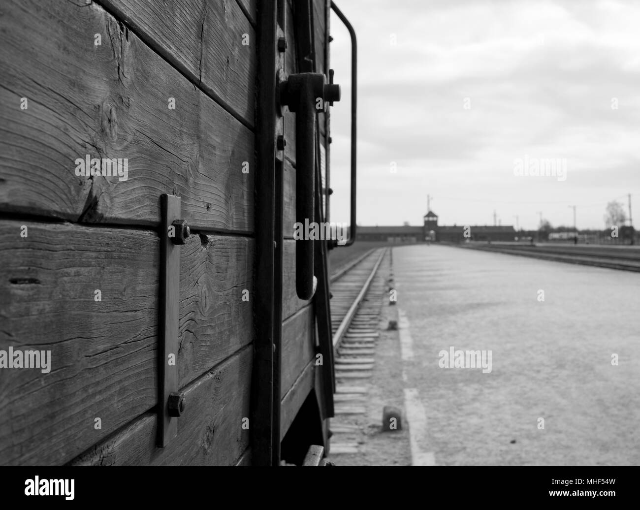 Main entrance to Auschwitz Birkenau Concentration Camp. In foreground, cattle car used to bring victims to the gas chambers. Monochrome photo. - Stock Image