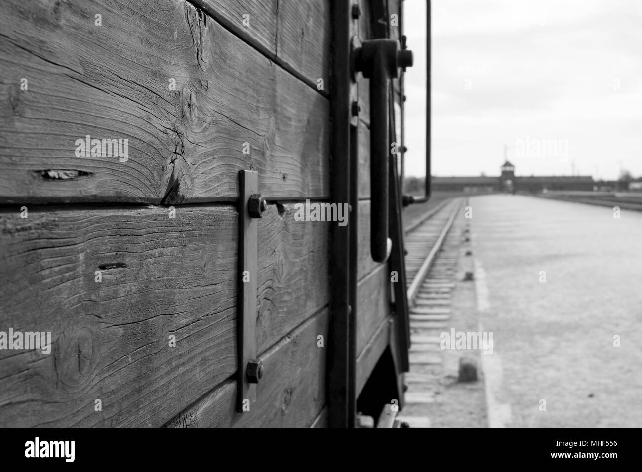 Eentrance to Auschwitz Birkenau Concentration Camp. In foreground is railway cattle car used to bring victims to the gas chambers. Monochrome photo. - Stock Image