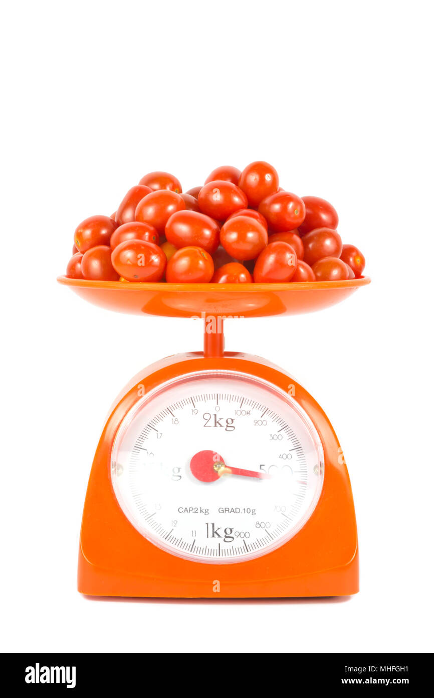 many fresh small tomato lying on weight scale - Stock Image
