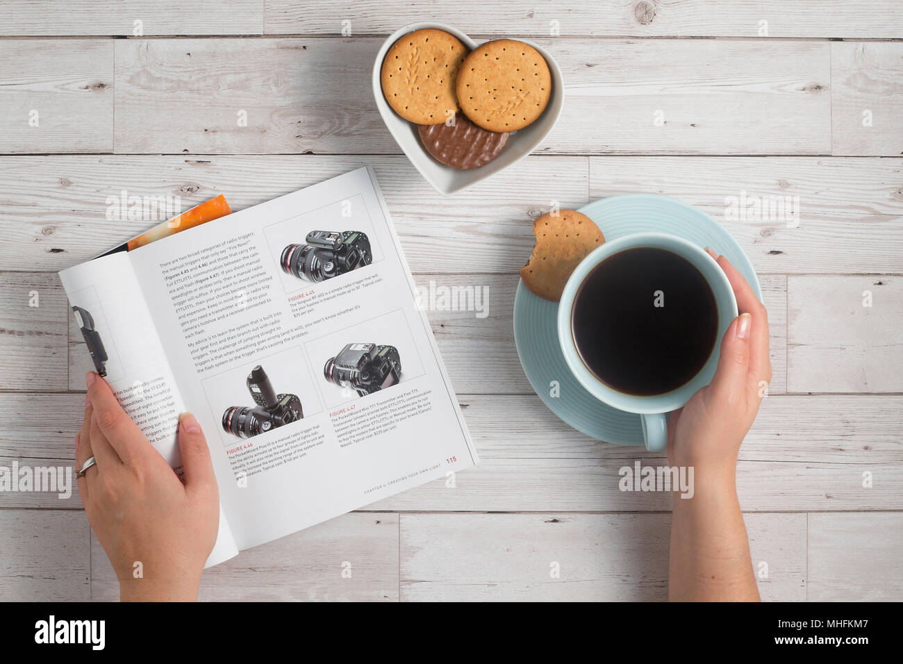 early morning enjoying coffee and reading about  photography - Stock Image