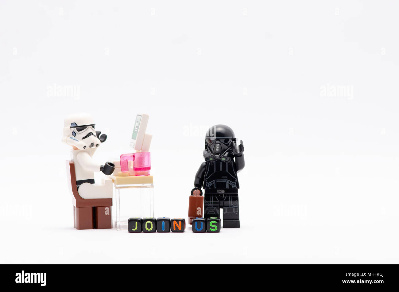mini figure of storm trooper on chair and death trooper with word join us. Lego minifigures are manufactured by The Lego Group. - Stock Image