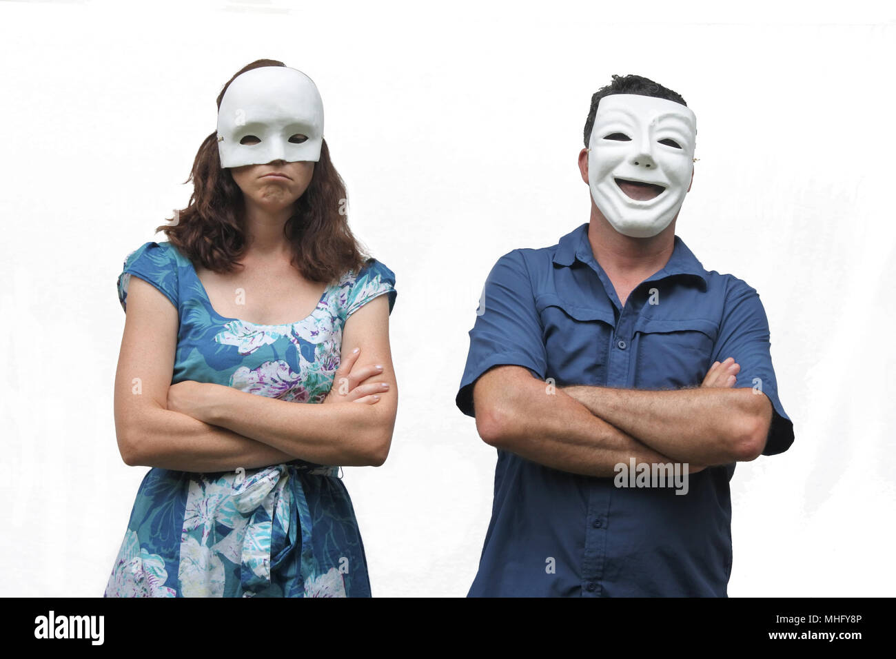 Confident man wearing a happy face mask standing beside a unconfident woman who wearing a sad face mask. Real people. Copy space - Stock Image