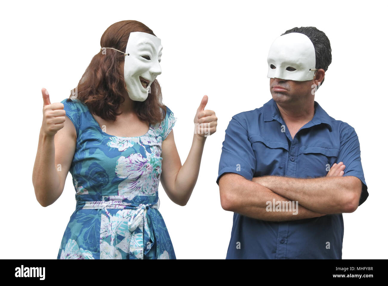 Woman wearing a happy face mask pointing thumbs up at a man who wearing a sad face mask. Real people. Copy space - Stock Image