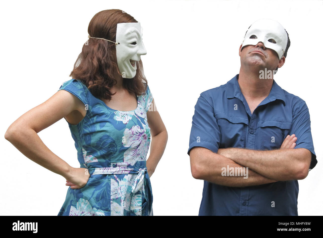Confident woman wearing a happy face mask looks at at unconfident man who wearing a sad face mask. Real people. Copy space - Stock Image
