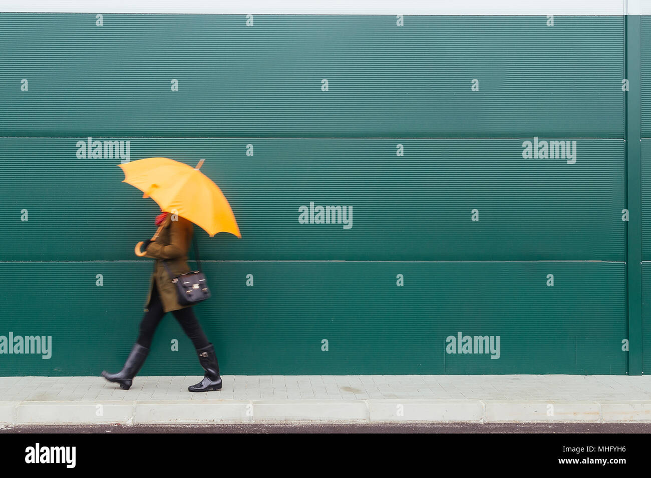 Girl with yellow umbrella walks by green wall - Stock Image
