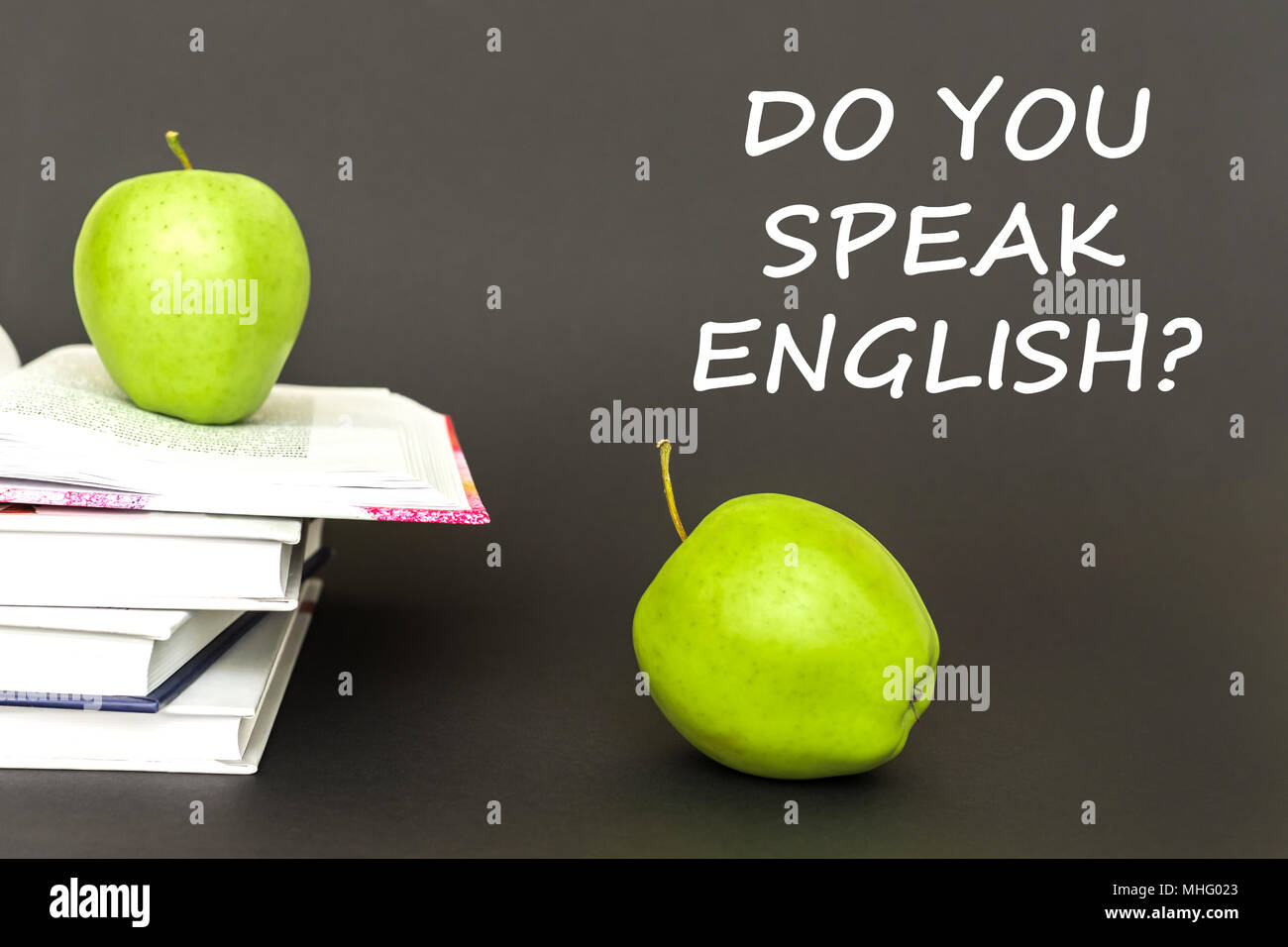 concept back to school, text do you speak english, two green apples, open books on gray background - Stock Image