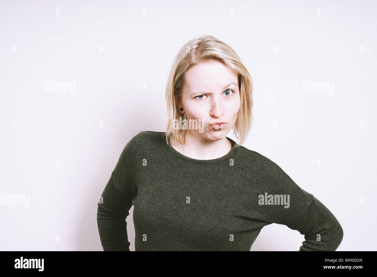 skeptical young woman grimacing making a funny face - Stock Image