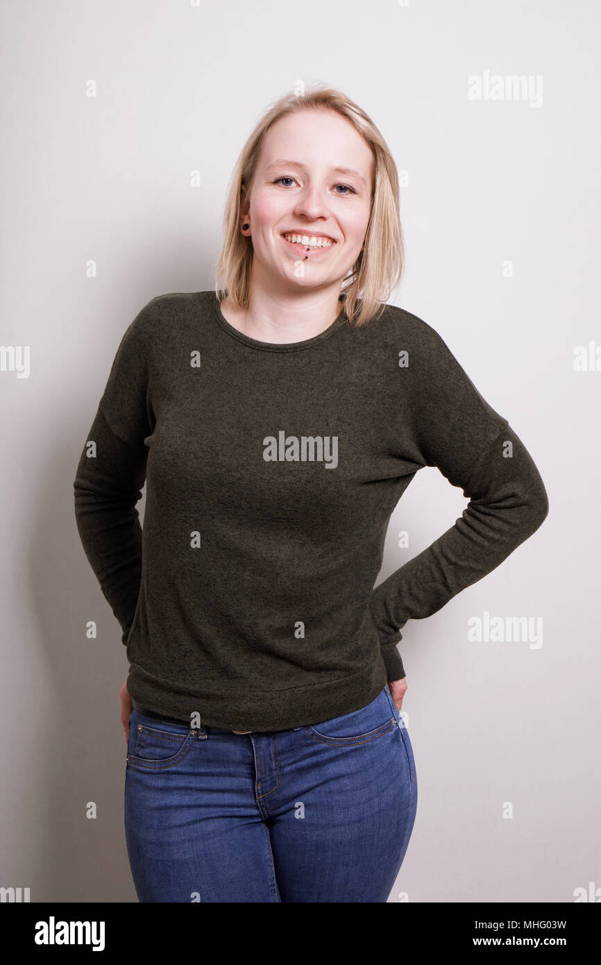 young blond millennial woman smiling, three quarter length real people portrait - Stock Image