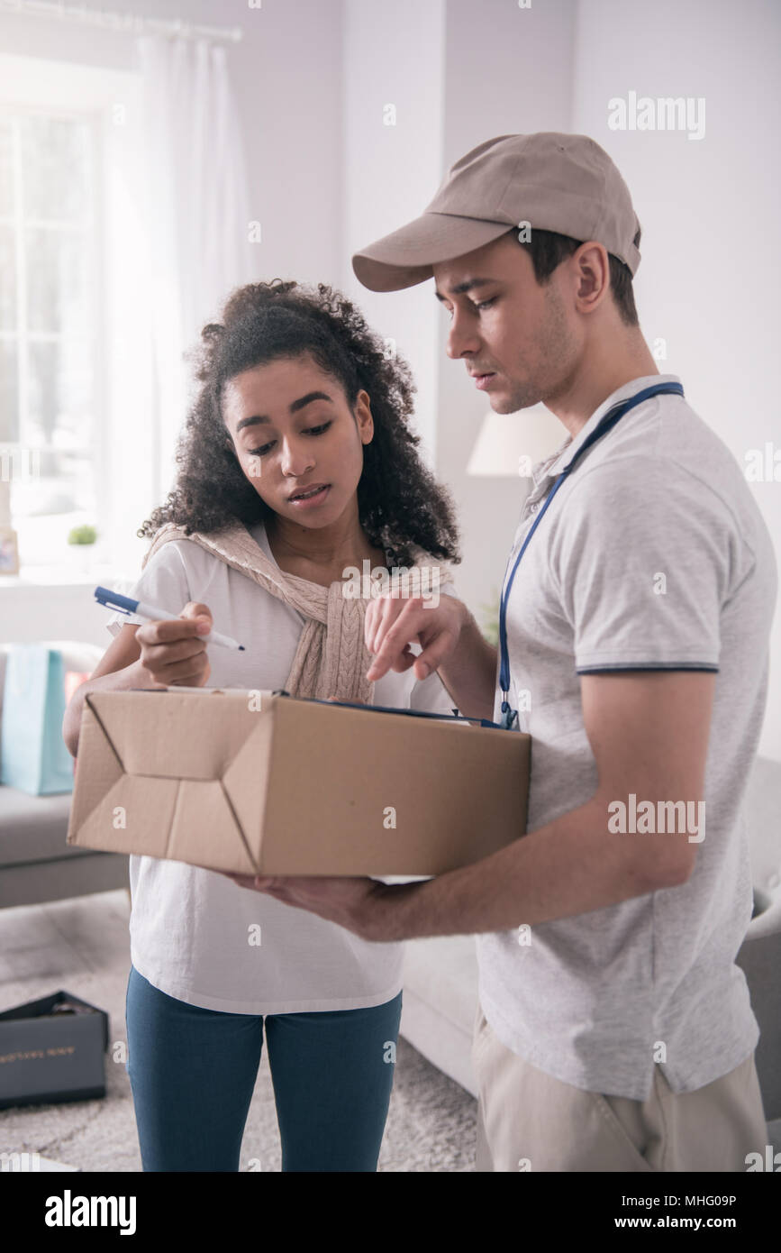 Pleasant good looking woman receiving the package - Stock Image