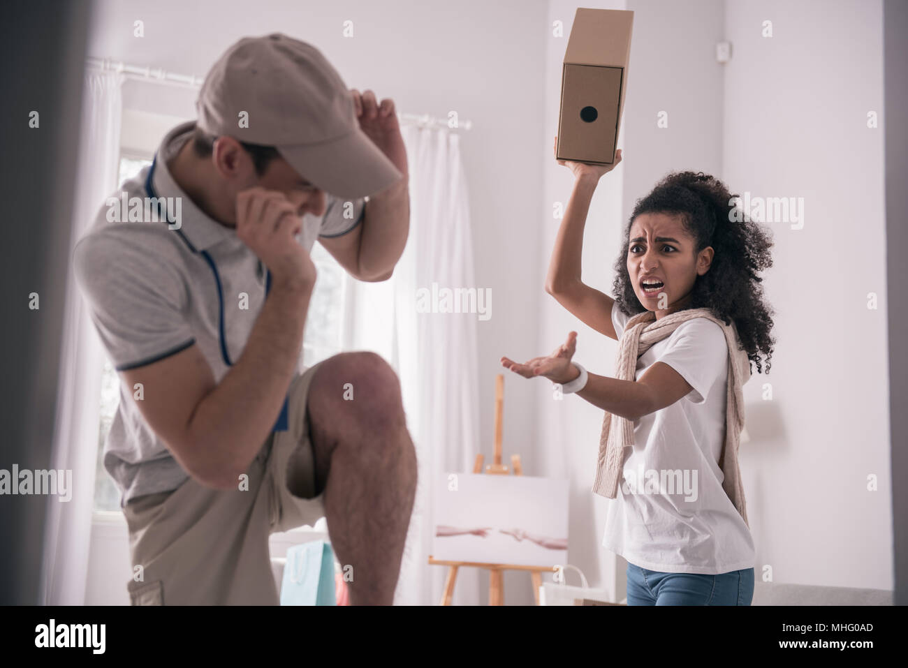 Angry young woman shouting at the courier - Stock Image
