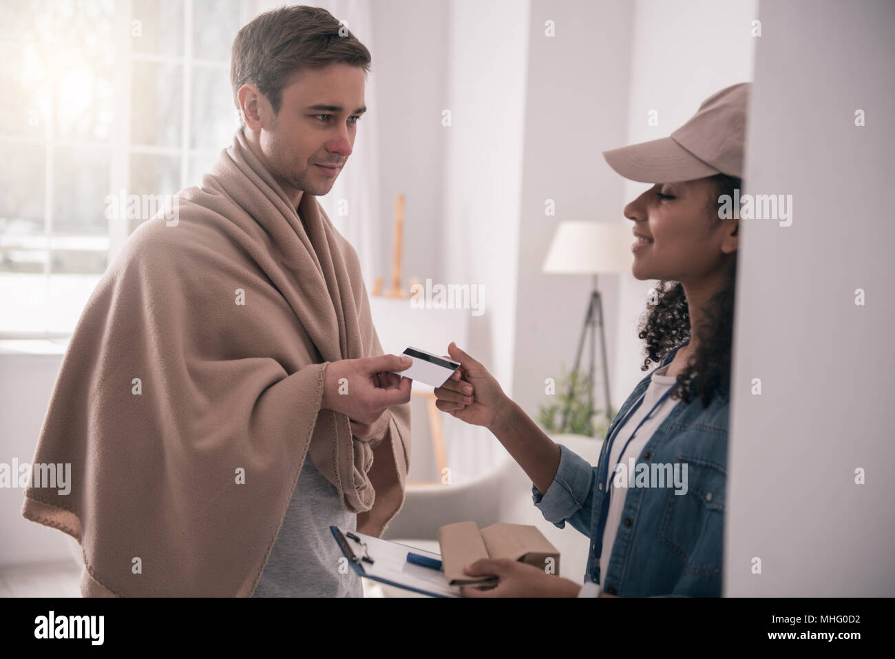 Positive nice woman taking a credit card - Stock Image