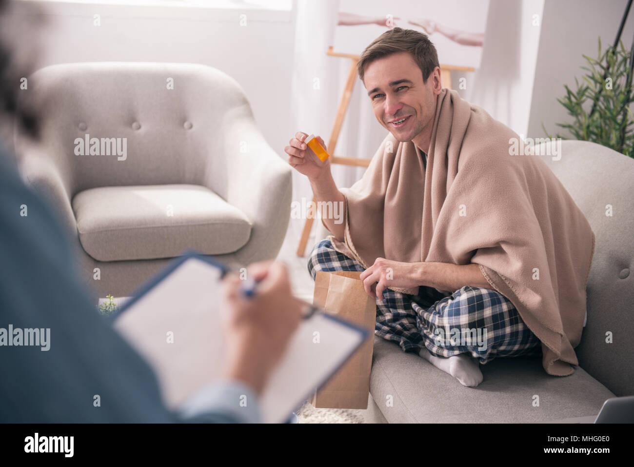 Joyful positive man holding his medicine - Stock Image