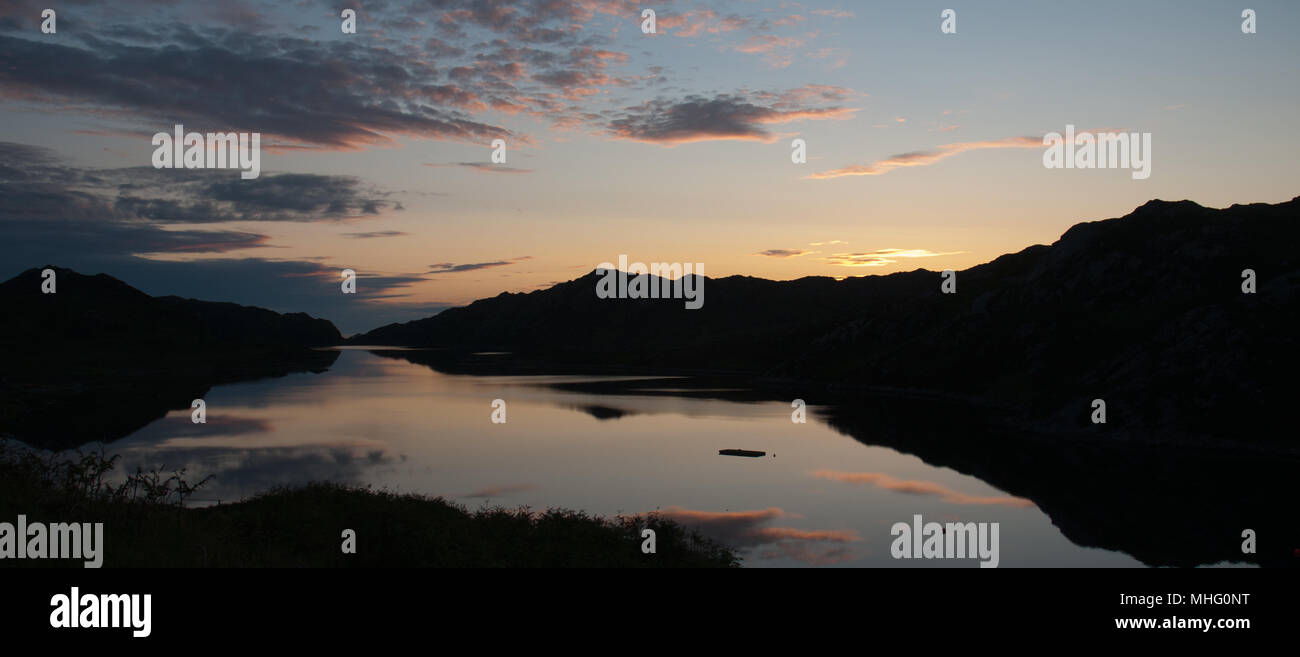 Sunset with silhouetted hills around Loch a'Chadh-Fi, Ardmore, Scotland - Stock Image