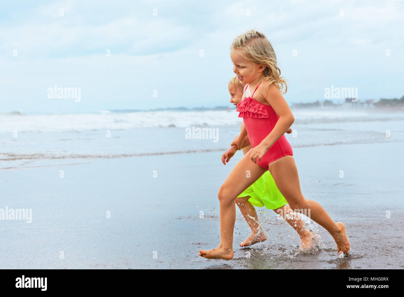 Happy barefoot kids have fun on sunset beach walk. Run by water pool along sea surf and jump. Family travel lifestyle, swimming activities - Stock Image