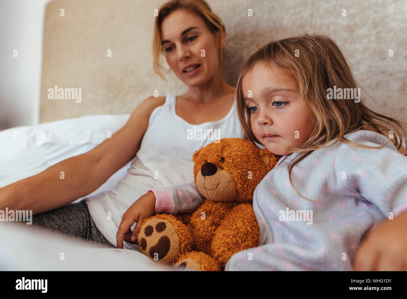 Little girl reading an interest book sitting on the bed with her mother. Mother and daughter reading a book in bed. - Stock Image