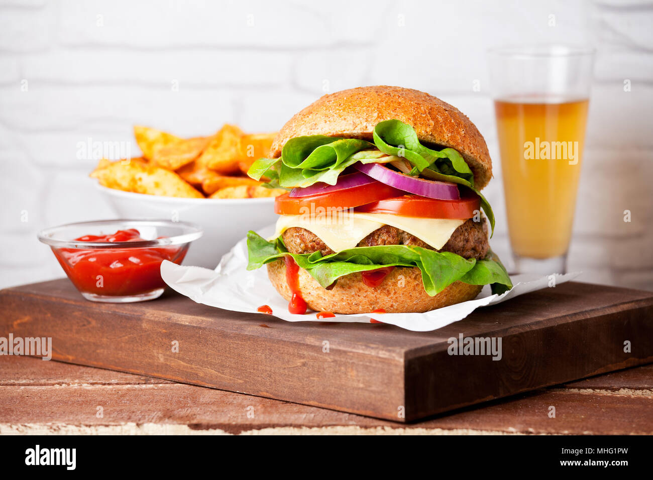 Homemade burger with hot potatoes and cold beer - Stock Image